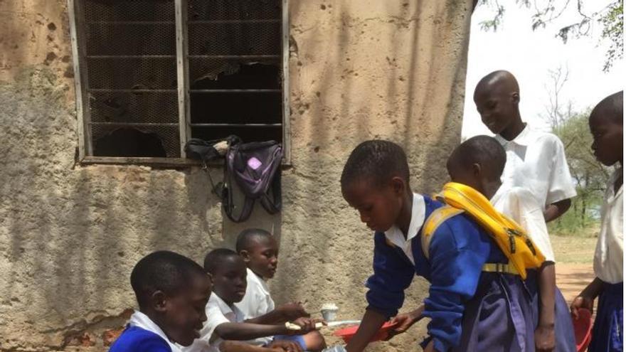 Niños reciben una ración de comida en una escuela de Tanzania que participa del programa alimentario de EEUU.