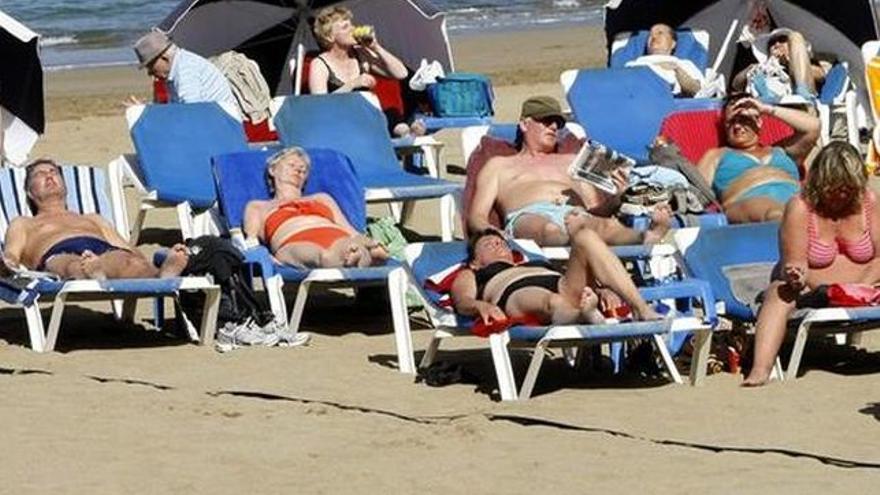 Turistas toman el sol en una playa canaria, en una imagen de archivo