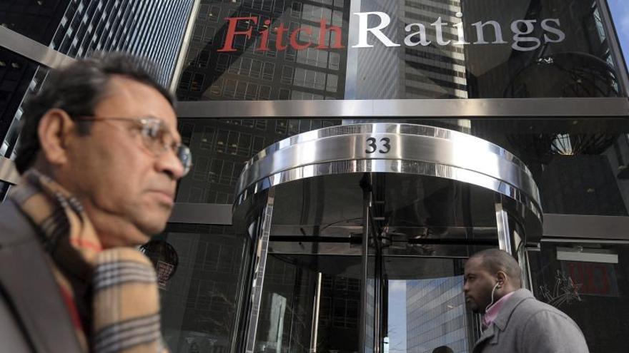 Dos viandantes pasan frente a la entrada de la sede de la agencia de calificación Fitch en Nueva York.