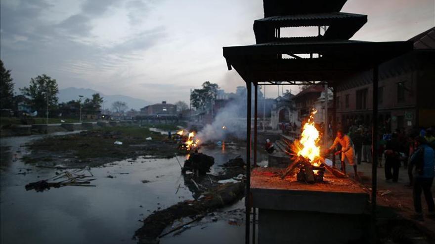 Un sacerdote prepara el fuego para la cremación de una de las víctimas del seísmo de Nepal, en el centro de incineraciones de Pashupat, en Katmandú. EFE.