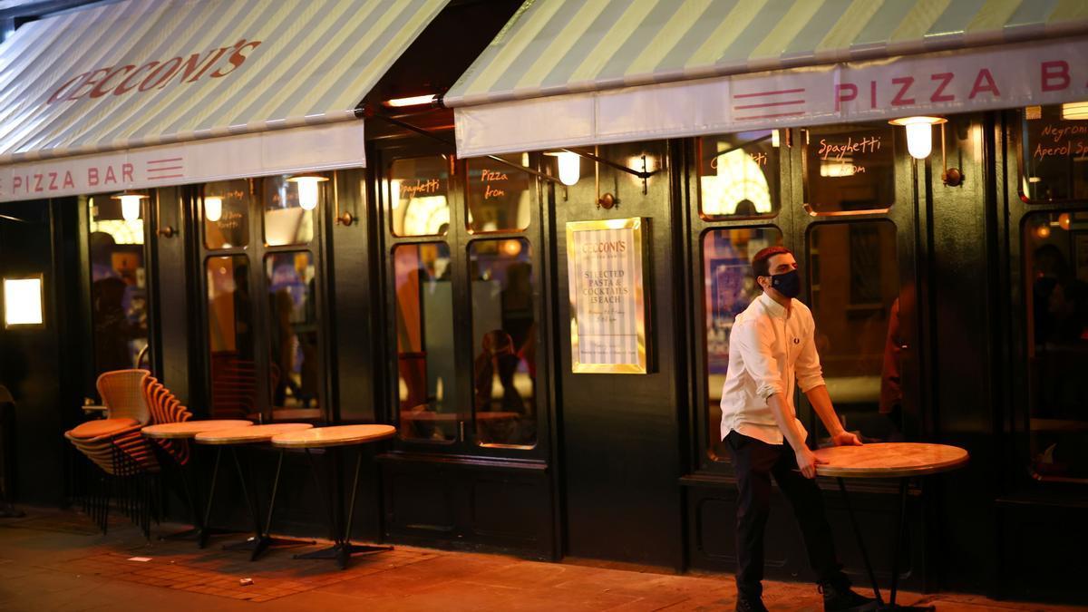Un camarero echando el cierre a su bar en el Soho, Londres