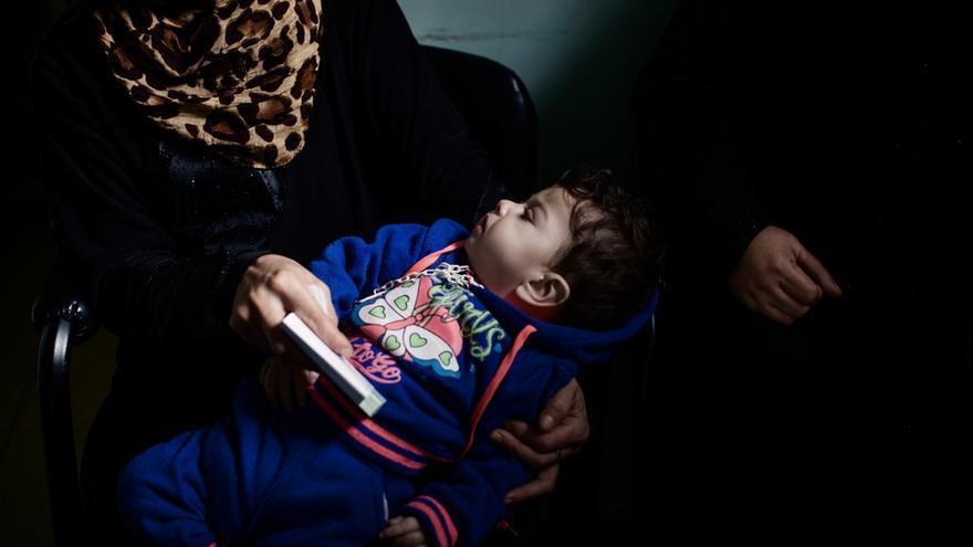 ACNUR estima que el 70% de los 42.000 niños nacidos de padres sirios en el Líbano desde que comenzó la guerra de Siria en 2011 no están registrados y, por tanto, expuestos al riesgo de una vida de la apátrida. Una mujer siria sostiene entre sus brazos a su hijo en la sala de espera de la unidad de maternidad de MSF en el campo de Chatila. Fotografía: Diego Ibarra Sánchez