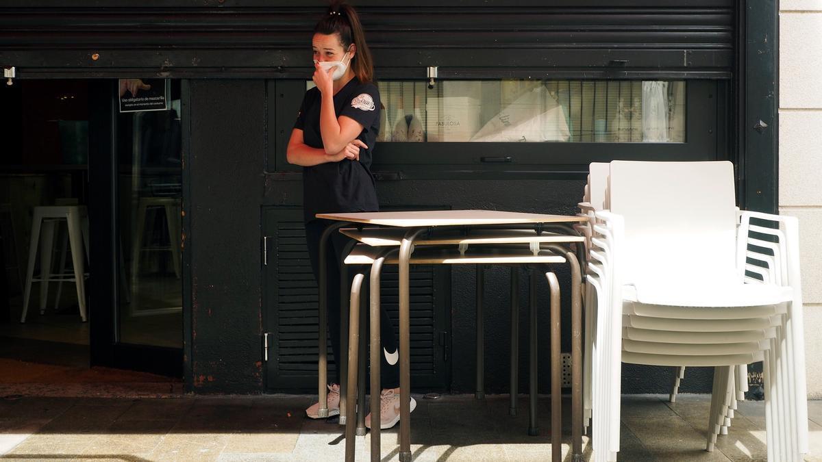 Una trabajadora junto al local en el que trabaja cerrado por coronavirus en el barrio de A Milagrosa en Lugo.