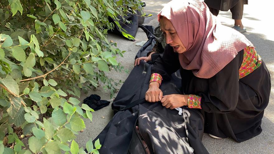 Una mujer llora junto al cuerpo de una víctima del atentado en el aeropuerto de Kabul.