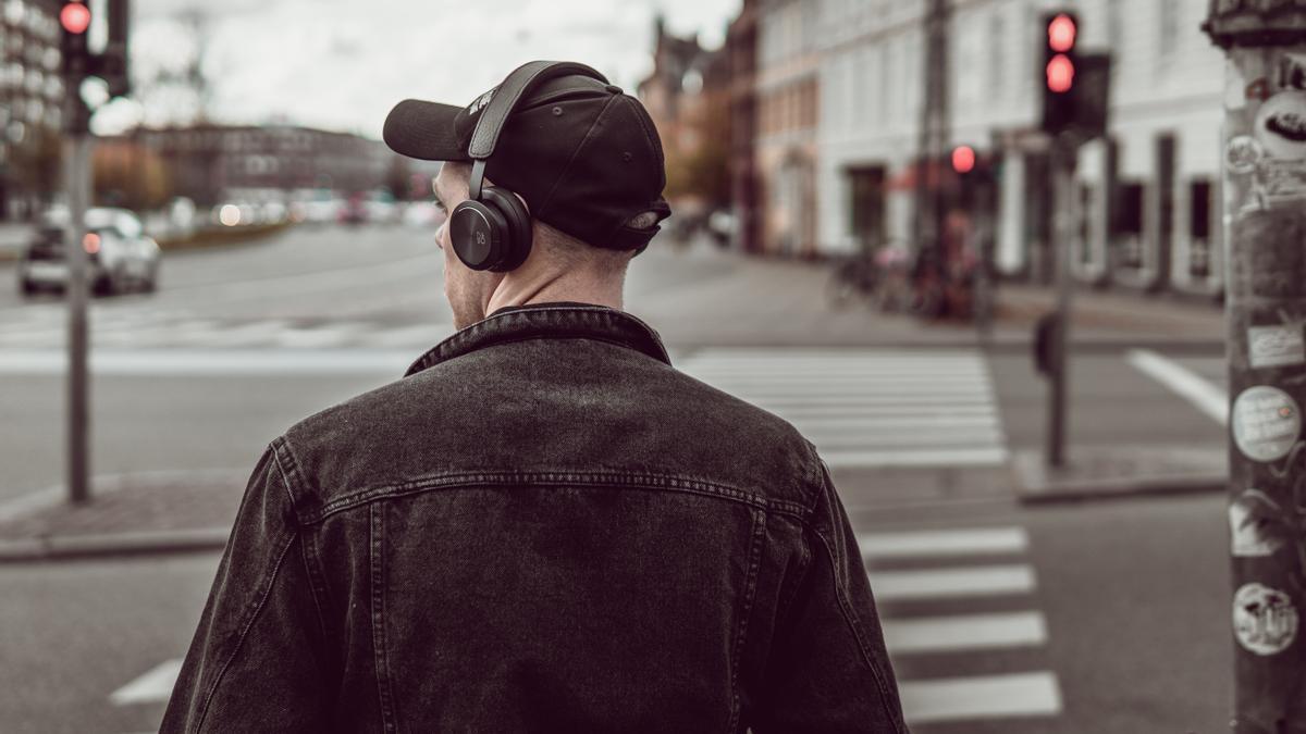 Un peatón cruza la calle con auriculares.