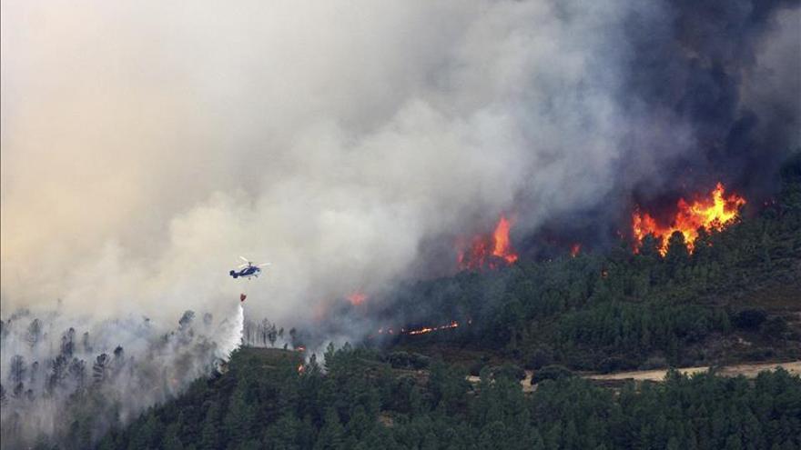 Vista de un helicóptero, realizando una descarga para controlar el incendio forestal declarado ayer en Acebo (Cáceres). El fuego ha quemado ya más de 5.000 hectáreas en Sierra de Gata. / EFE.