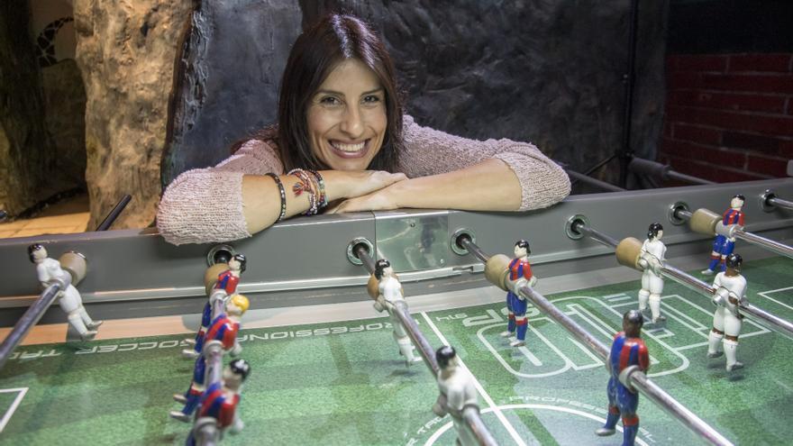 Miriam Navarro, junto a un futbolín multicultural con jugadores y jugadoras de distintas razas.