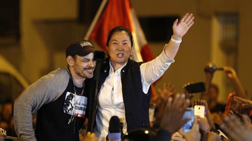 Keiko Fujimori (c), fue registrada el pasado 29 de noviembre, junto a su esposo, Mark Vitto (i), al saludar a su salida del penal de mujeres Santa Mónica de Chorrillos, donde permaneció trece meses en prisión preventiva, en Lima (Perú).