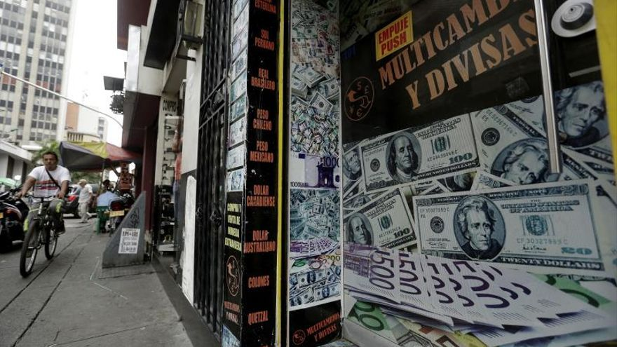 Ciudadanos pasan junto a una casa de cambio de divisas este miércoles, en Cali (Colombia).