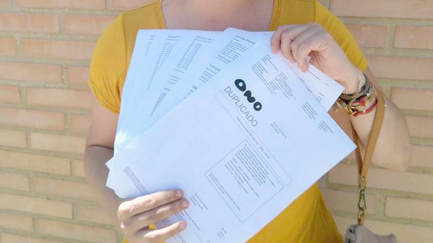 Nuria muestra los recibos de las compañías telefónicas