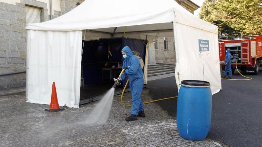Los bomberos desinfectan una carpa en la que se toman muestras de SARS-CoV-2 en un hospital del área sanitaria de Ferrol (A Coruña).