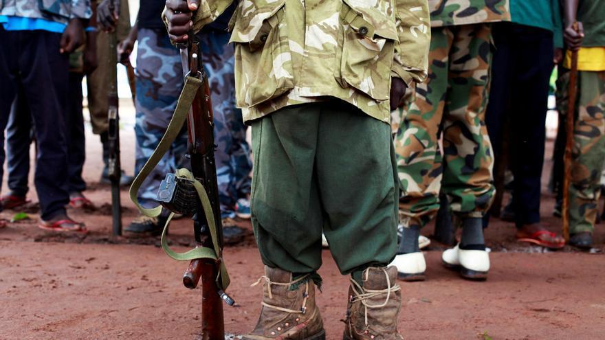 Un ex niño-soldado sostiene un arma durante la ceremonia de liberación de niños soldados, en las afueras de Yambio, Sudán del Sur // REUTERS / Andreea Campeanu