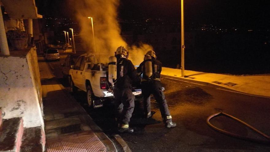 Dos bomberos durante las tareas de extinción del incendio registrado en la madrugada de este domingo en un vehículo en la zona de Montaña Tenisca.