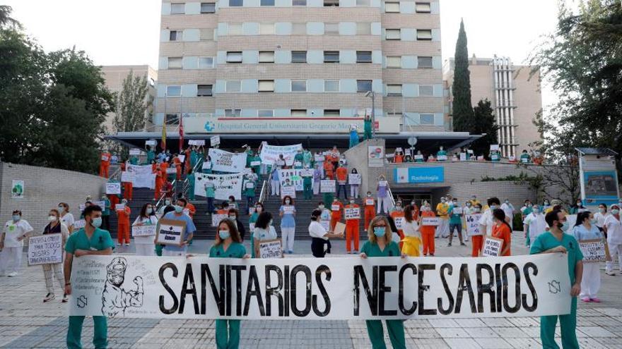 """Miembros del personal sanitario del Hospital Gregorio Marañón posan con una pancarta en la que se lee """"Sanitarios necesarios"""""""