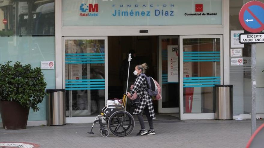 Una mujer con una máscara sanitaria porta una silla de ruedas en los exteriores del Hospital Universitario Fundación Jiménez Díaz de Madrid.