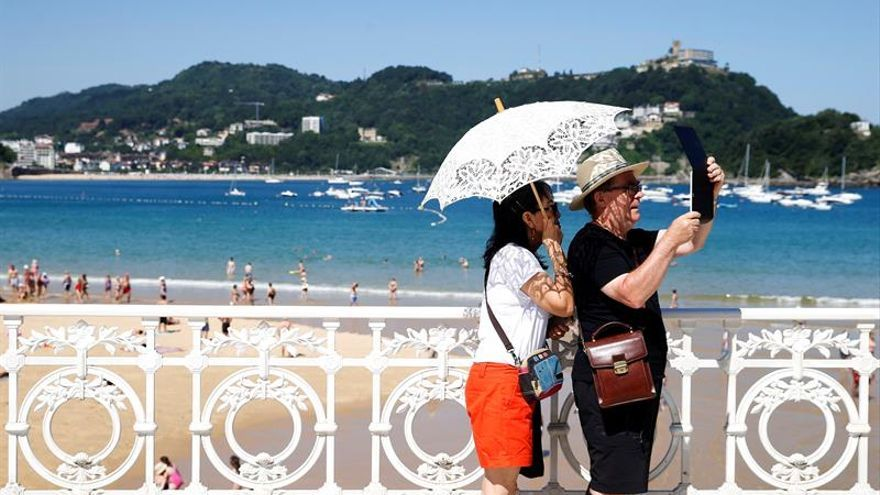 Una pareja de turistas en la playa de la Concha de San Sebastián.
