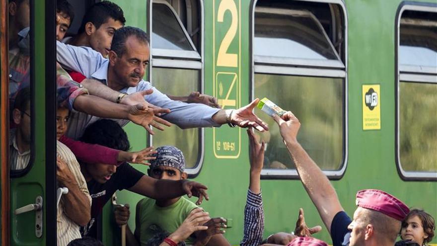 Un policía entrega zumo y frutas a los refugiados en la estación ferroviaria de Bicske (Hungría). / Efe.