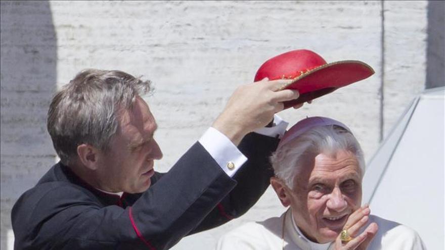 Benedicto XVI recibe la ayuda de su secretario personal.