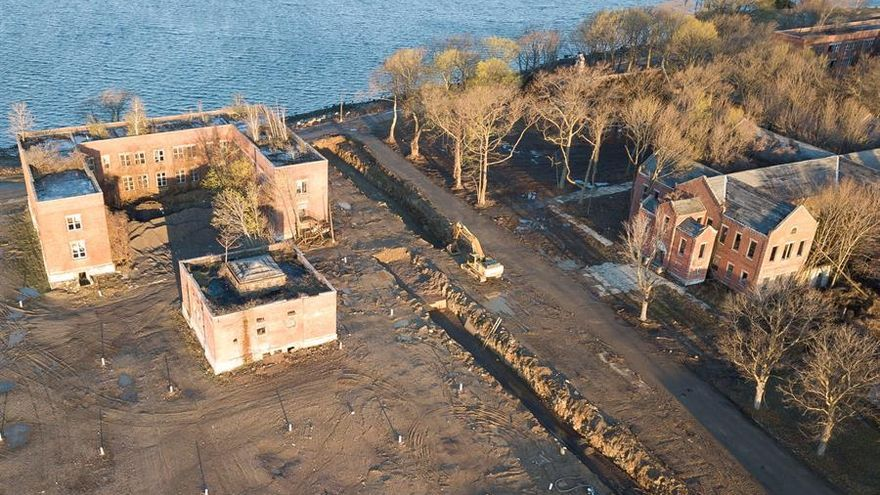 In an aerial photograph, a backhoe is seen next to large burial trenches and abandoned buildings on Hart Island, located in the Long Island sound, off the coast of the Bronx, New York, USA, on 10 April 2020. EFE/EPA/JUSTIN LANE