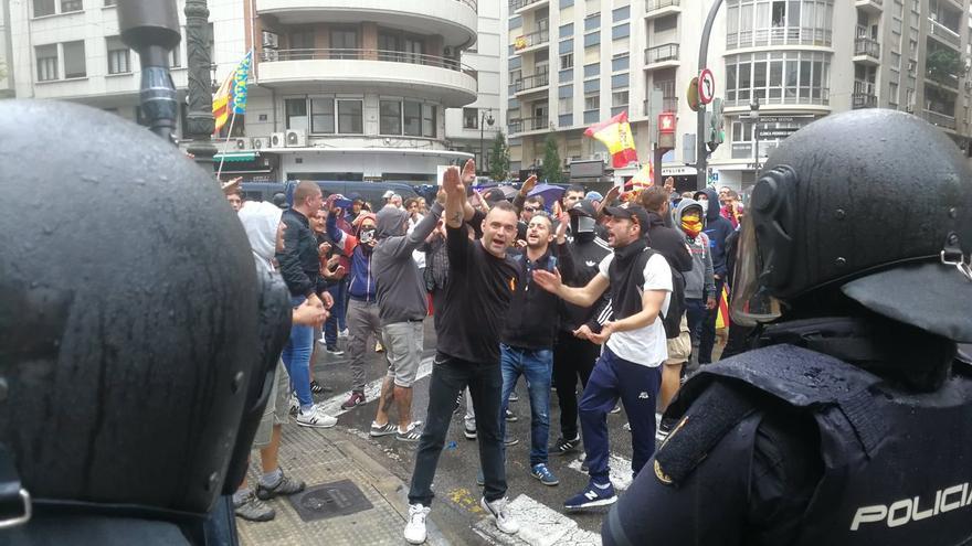 Los ultras con el brazo en alto custiodados por la Policía