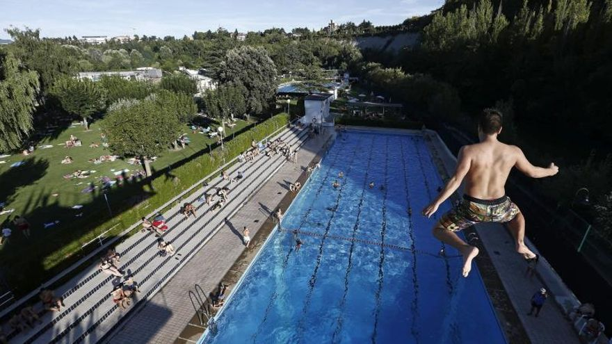 Un joven salta del trampolín a la piscina.