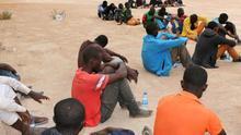 Un grupo de inmigrantes esperan en un centro de internamiento de una ciudad libia, tras ser detenidos cuando se dirigían a la ciudad de Zawara para abordar una embarcación precaria para dirigirse a Europa.