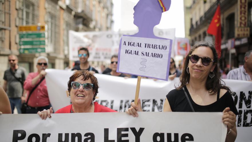 Dos mujeres piden igualdad salarial entre hombres y mujeres en la manifestación del Primero de Mayo.