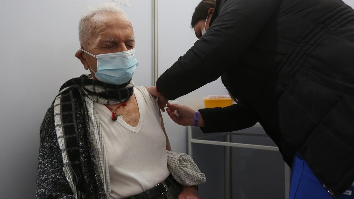Un adulto mayor recibe una dosis de refuerzo de AztraZeneca, en un centro de vacunación contra la COVID