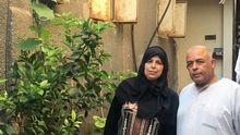 Juma y Atiat junto a la entrada de su casa en la que viven 12 miembros de su familia.