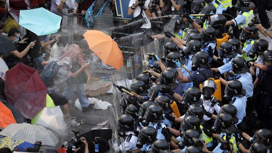 Manifestantes chinos se defienden con paraguas de la represión policial con gas pimienta durante las protestas en Hong Kong Foto: Vincent Yu, File/AP
