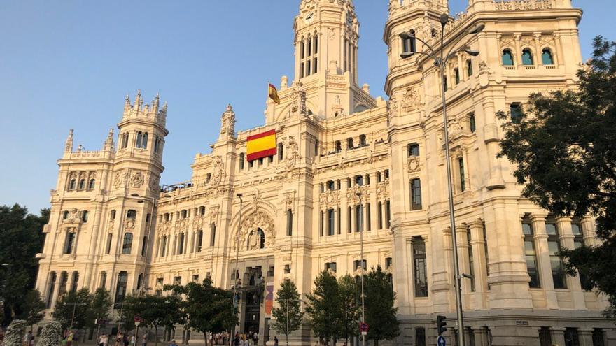El nuevo Ayuntamiento de Madrid despliega una bandera de España en la fachada del Palacio de Correos.