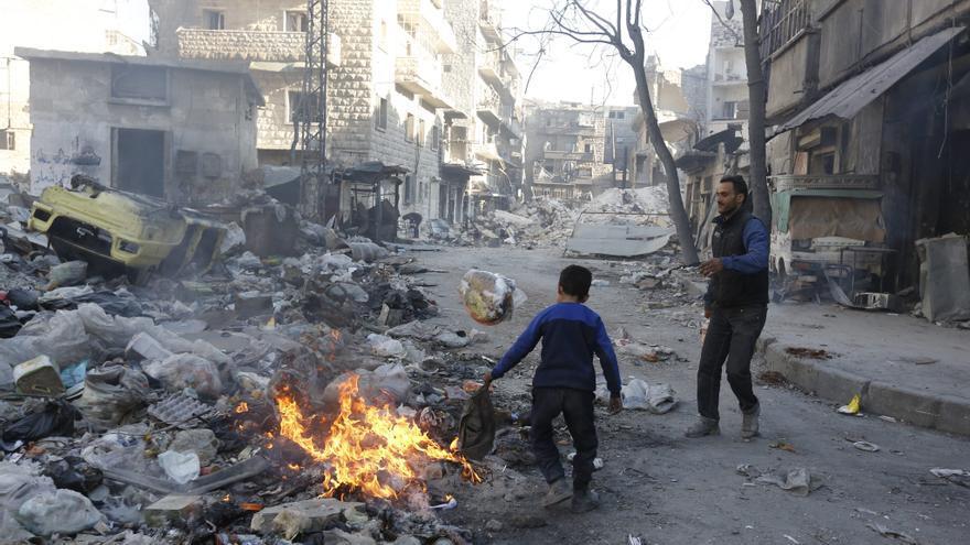 Un niño enciende una fogata en el barrio Bustan Alqasr en Alepo (Siria)  // EFE
