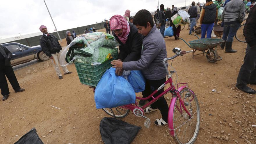 Refugiados sirios cargan sus provisiones de invierno en una bicicleta en el campo de refugiados de Zattari, en Jordania