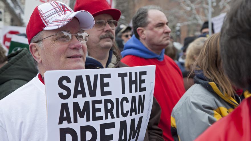 """Un hombre en una protesta sostiene una pancarta que reza: 'Salven el sueño americano"""""""