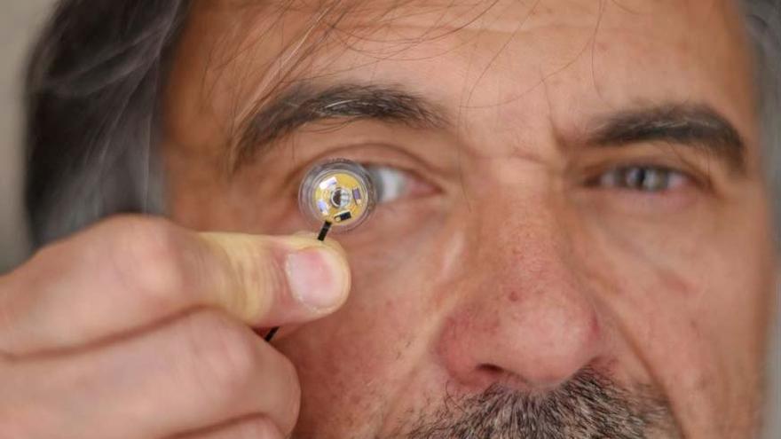Jean-Louis de Bougrenet de la Tocnaye, uno de los investigadores franceses, posando con la lentilla de su creación