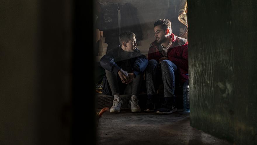 Halid Nadarevic, un niño bosnio de 11 años, junto a Ali Hassan, un joven pakistaní de 21 años. Hassan vive con varios compañeros pakistaníes en una casa abandonada en la localidad de Trzac, Bosnia, esperando la oportunidad de volver a intentar cruzar la frontera con Croacia. Nadarevic es un niño cuya familia ayuda a la población migrante, al igual que muchos vecinos del pueblo.