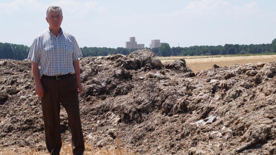 Un vecino junto a los montones de basura acumulada en Fuentepelayo (Segovia), en julio de 2016.