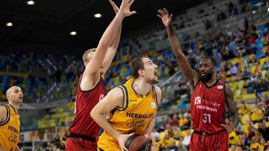 El jugador del Herbalife Gran Canaria Balbin, con la pelota ante la defensa de Clark Daniel y Eyenga, de Montakit Fuenlabrada.