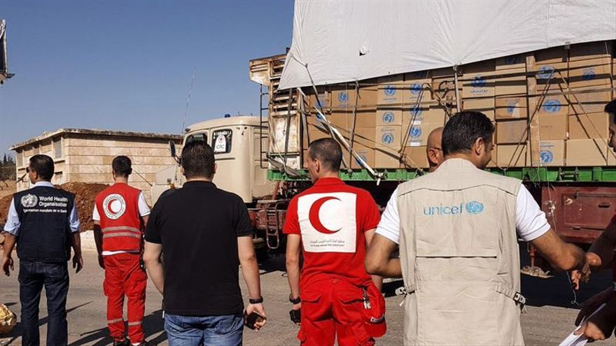 Fotografía cedida este lunes por la Media Luna Roja Siria, que muestra un convoy de camiones antes de partir para entregar ayuda humanitaria hoy en el área rural de Alepo (Siria). EFE