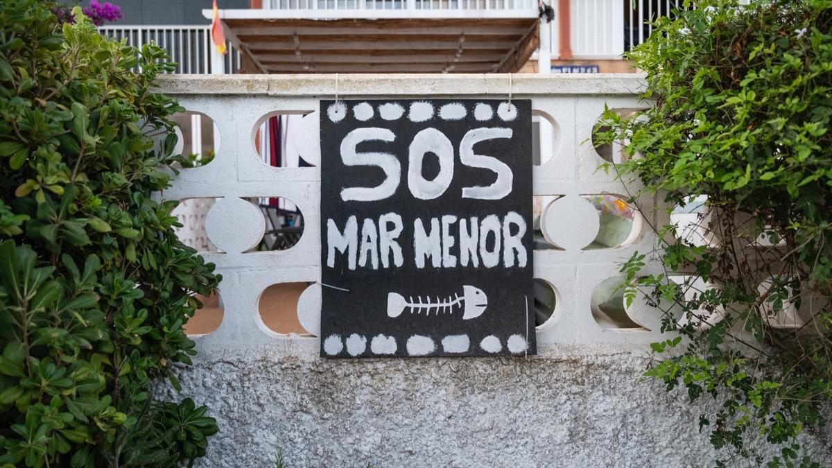 Una pancarta colgada en la fachada de una casa frente al Mar Menor