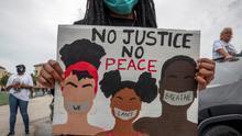 """Una manifestante sostiene una pancarta con el lema """"Sin justicia, no hay paz"""" durante una protesta por la muerte de George Floyd en Florida"""