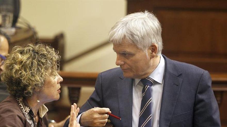 El vicepresidente y consejero de Educación del Gobierno de Canarias, José Miguel Pérez, conversa con la diputada María del Mar Julios, durante el pleno del Parlamento regional. EFE/Cristóbal García