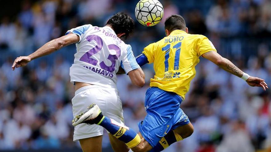 El defensa del Málaga Miguel Torres (i) y el centrocampista de la Unión Deportiva las Palmas Momo Figueroa (d), saltan por el balón durante el partido correspondiente a la trigésima octava y última jornada de Liga de Fútbol en el estadio de la Rosaleda en Málaga. EFE/Jorge Zapata