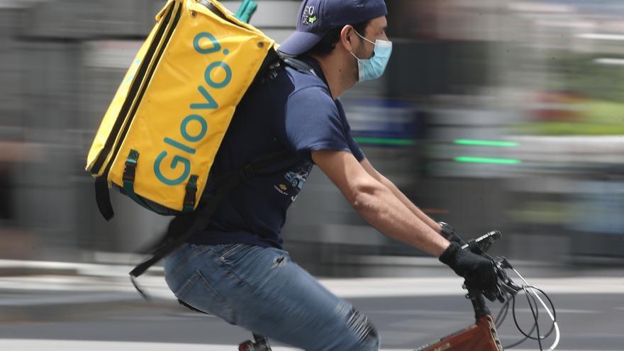 Un repartidor de Glovo monta una bicicleta durante su jornada laboral.