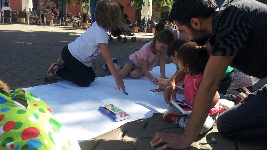 Niños y niñas pintando carteles para la manifestación de esta tarde