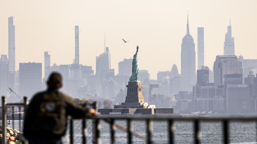 Un hombre observa la Estatua de la Libertad desde Jersey City.