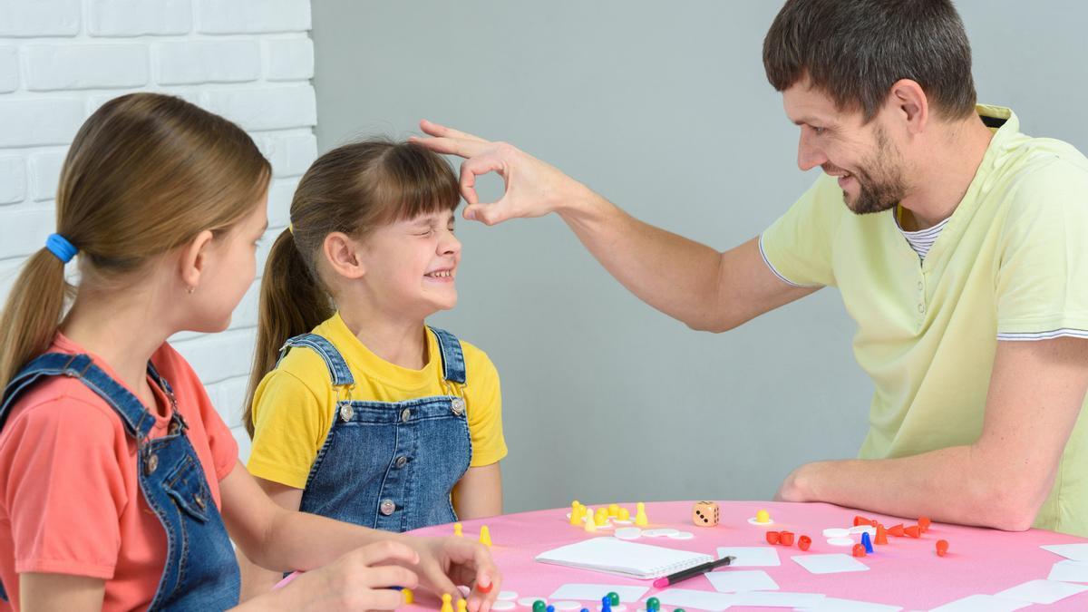 Un padre juega con sus hijas a juegos de mesa