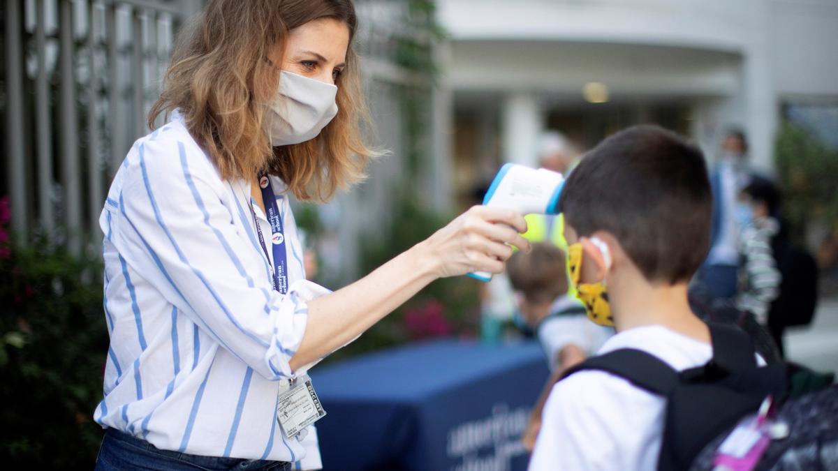 Una trabajadora toma la temperatura a un niño a la entrada del colegio privado internacional American School of Barcelona, situado en Esplugues de Llobregat (Barcelona).