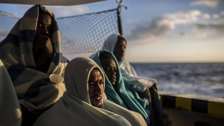 Algunas de las personas rescatadas por Proactiva Open Arms el pasado 21 de diciembre miran el mar desde la cubierta del barco de rescate / Olmo Calvo