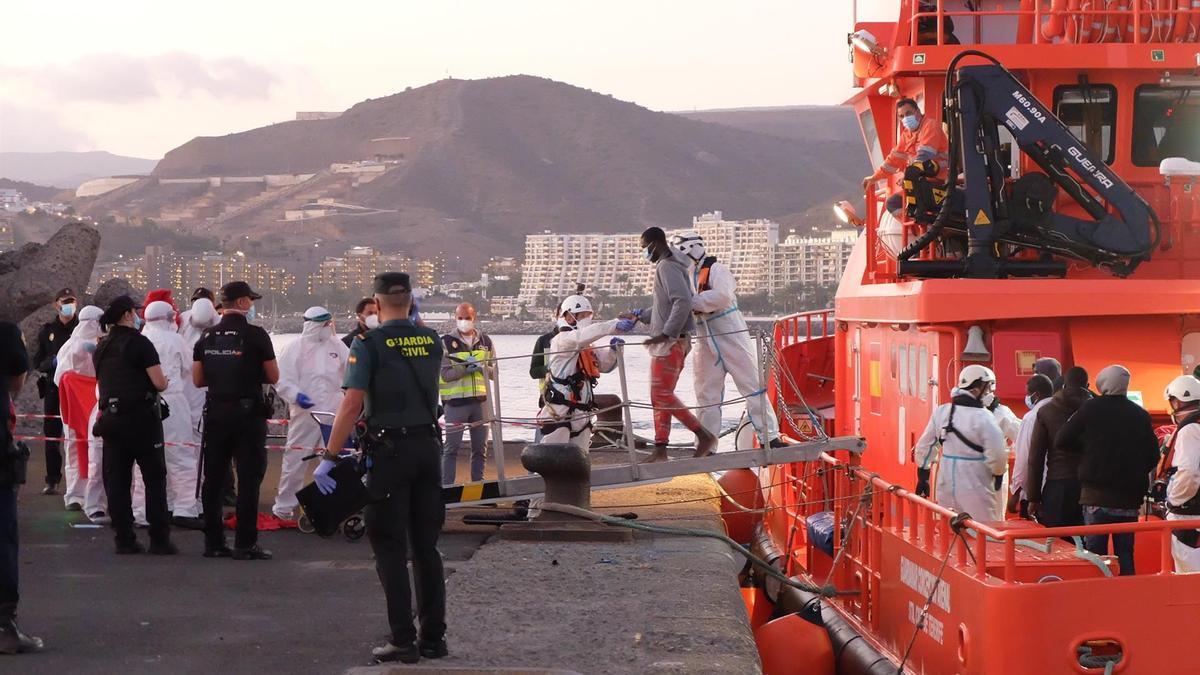 MIembros de la Cruz Roja ayudan a bajar del barco a migrantes en el puerto de Arguineguín